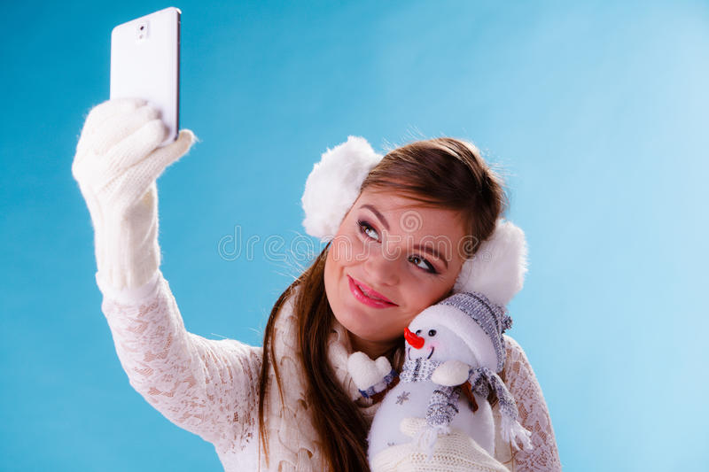 Woman with little snowman taking selfie photo. Pretty cute woman holding little snowman taking selfie self photo picture with camera. Attractive girl in stock images