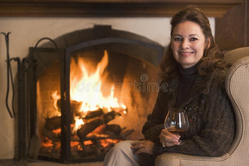 Woman in living room with drink smiling royalty free stock image