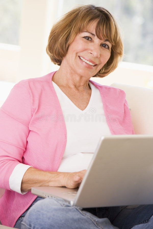 Woman In Living Room With Laptop Smiling Royalty Free Stock Photos