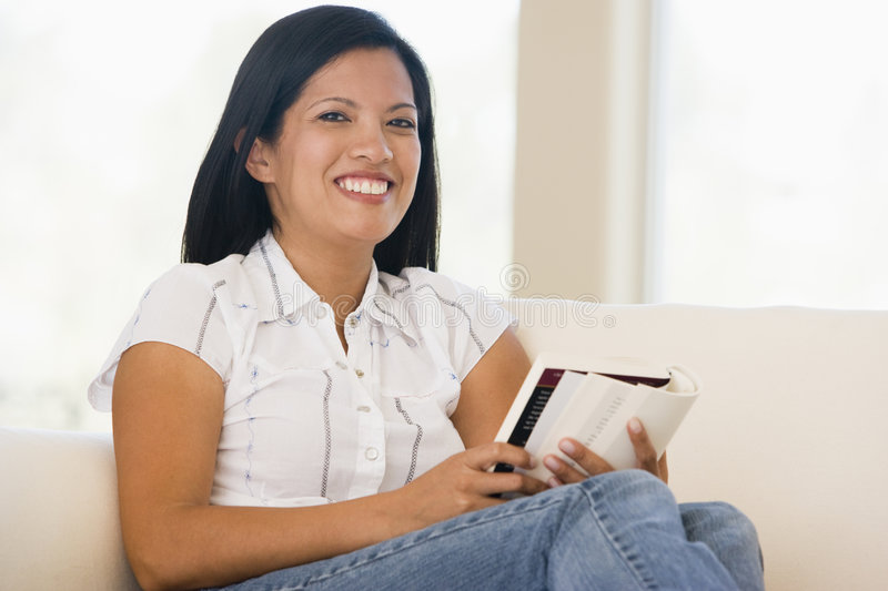 Woman in living room reading book smiling royalty free stock photo