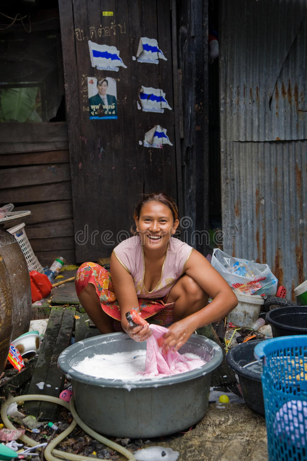 A woman living in a slum doing laundry stock photography