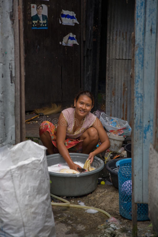 A woman living in a slum doing laundry stock image