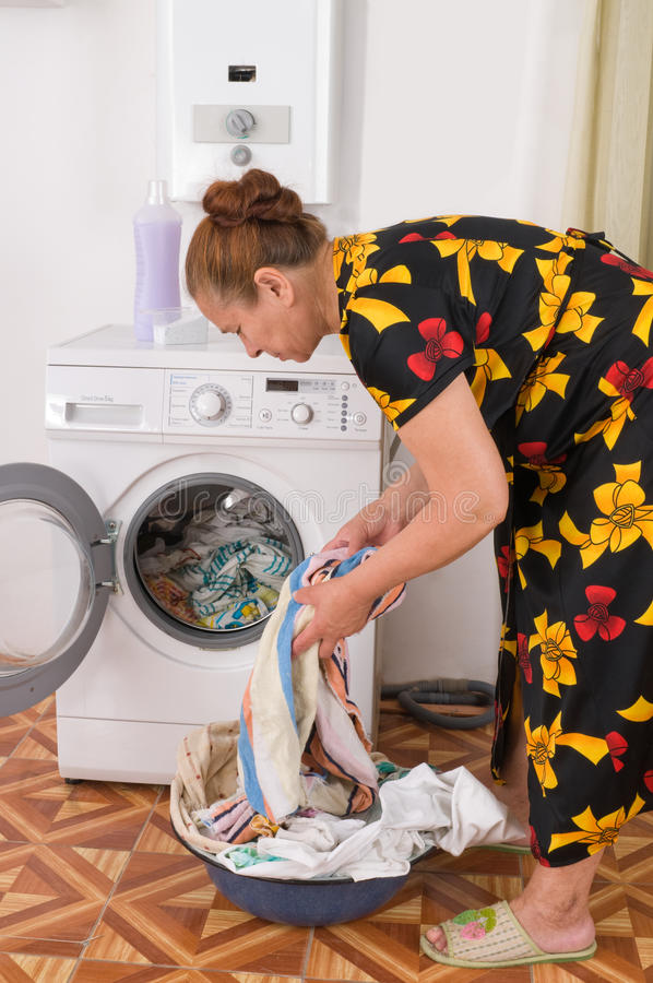The woman loads linen into a washing machine. royalty free stock photo