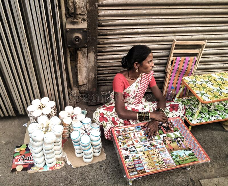 Woman in local market selling utensils on footpath stock photo