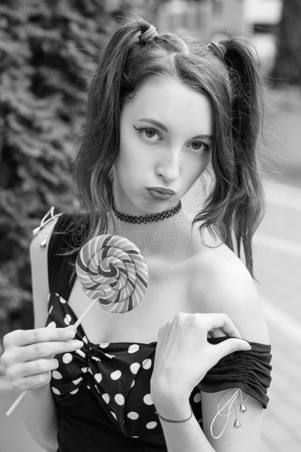 Woman with lollipop. Sensual young woman with lollipop in black dress posing on street, show her shoulder looking at camera, monochrome royalty free stock photography
