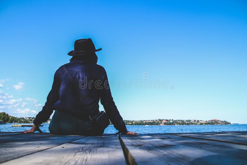 A woman lonely sitting on the wooden pier at the sea with blue sky. A woman lonely sitting on the wooden pier at the sea with blue sky, alone, back, background royalty free stock image