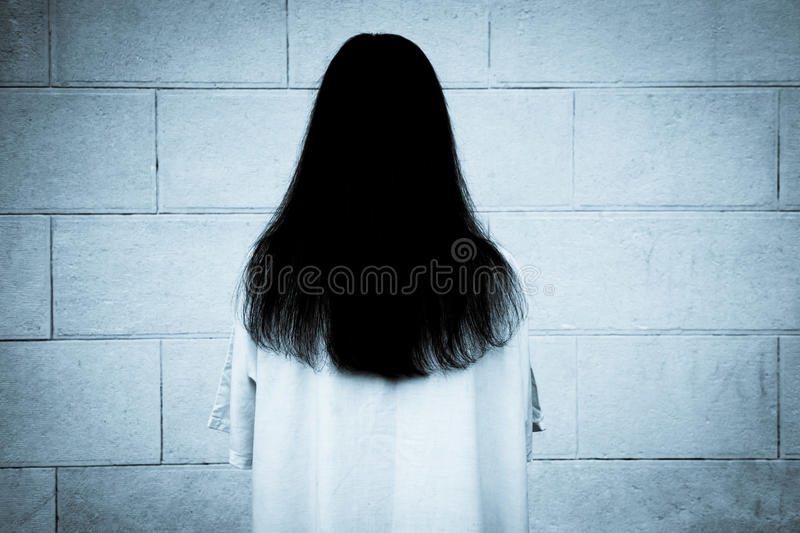 Woman with long black hair staring at the wall. Mysterious and spooky woman with long black hair and white dress, facing the wall royalty free stock photos