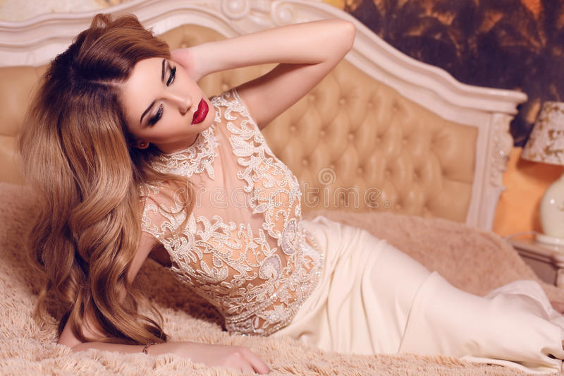 Woman with long blond hair in elegant beige dress. Fashion interior photo of beautiful sensual woman with long blond hair in elegant beige dress posing in stock images