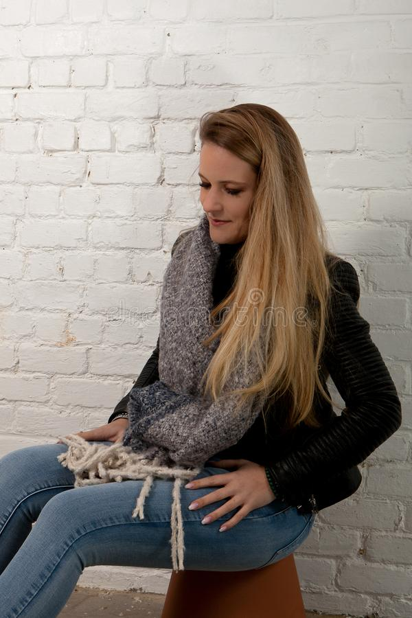 Blond woman sitting green eyes white brick wall. Woman with long blond hair and green eyes in leather jacket and knitted grey scarf for the winter sitting royalty free stock photography