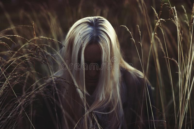 Woman with long blonde hair bowing her head in tall grass field in the dark. Face hidden in the shadow stock images