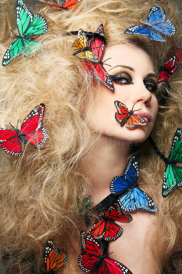 Woman with long curly hair with butterflies. royalty free stock image