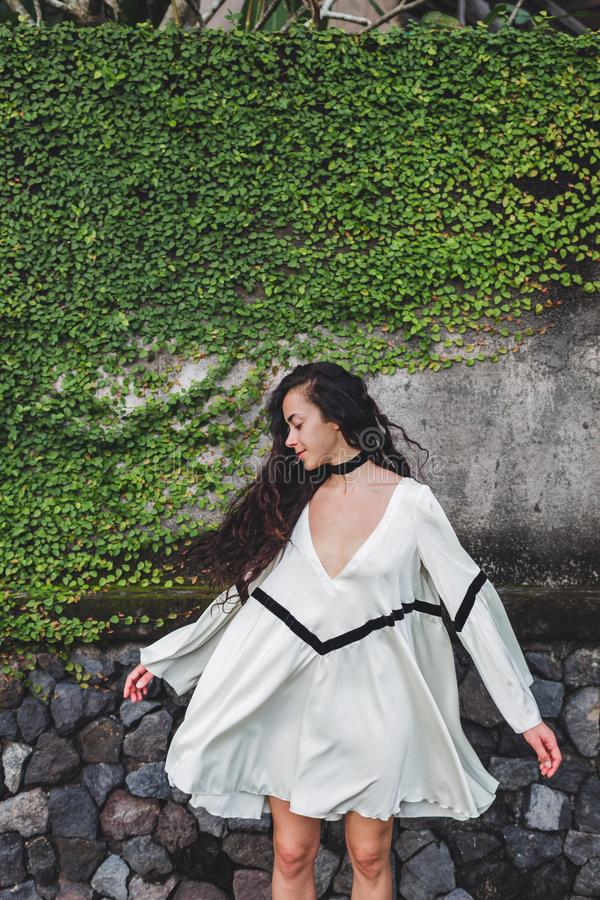 Woman with long curly hair in white light dress. Wind in hair. Background of concrete wall with green plants stock photos