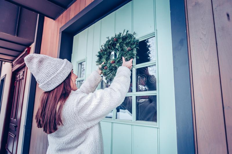 Woman with long dark hair putting Christmas wreath on front door stock photography