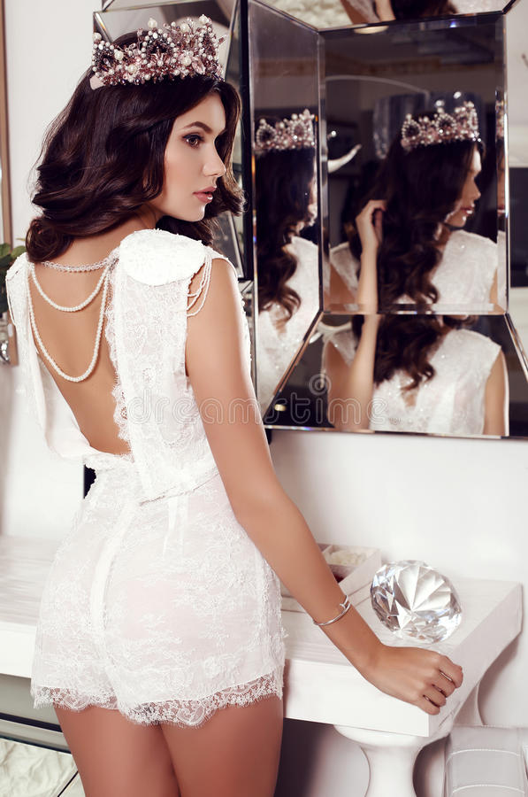 Woman with long dark hair wears elegant lace suit and precious crown royalty free stock images