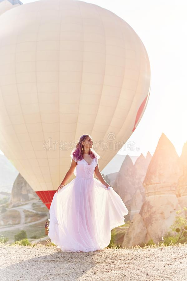 Woman in a long dress on background of balloons in Cappadocia. Girl with flowers hands stands on a hill and looks at large number. Woman in a long dress on stock photography