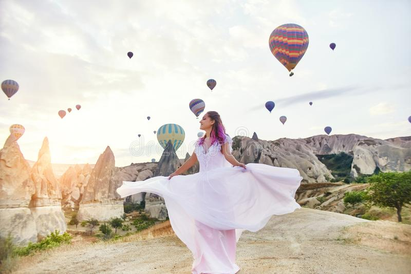 Woman in a long dress on background of balloons in Cappadocia. Girl with flowers hands stands on a hill and looks stock image