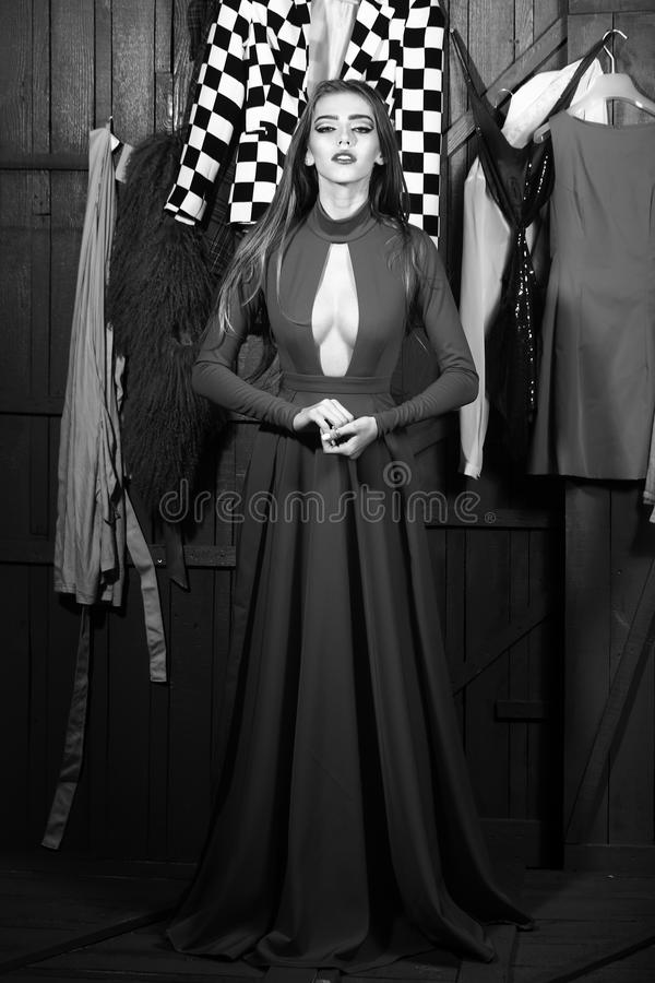 Woman in long dress. One sexual attractive diva young woman in long dress with deep low neck standing in wardrobe among many colorful bright clothes hanhing on royalty free stock images