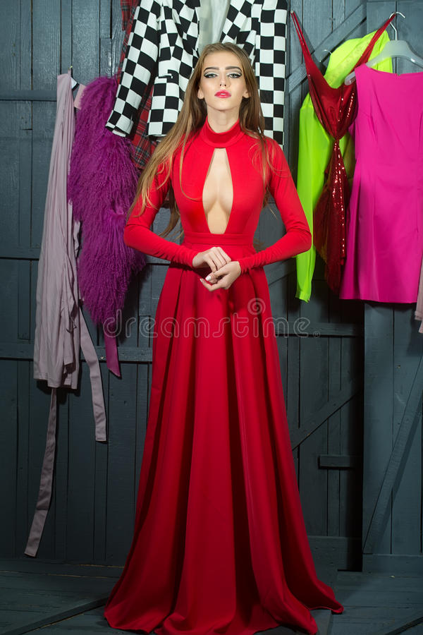 Woman in long dress. One sexual attractive diva young woman in long red dress with deep low neck standing in wardrobe among many colorful bright clothes hanhing royalty free stock photo