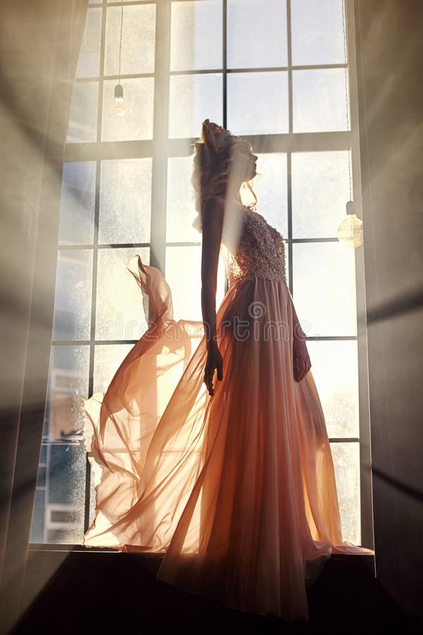 Woman in long dress stands at window in sunlight. Fairy Princess. Queen royalty free stock image