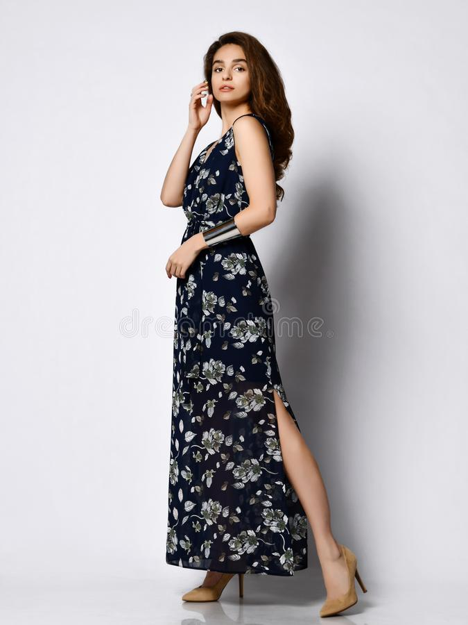 Woman in Long Floral Dress in Fashion Store - Portrait of girl in a clothes shop in a maxi summer dress. Sexy pretty woman pretty face wearing a dark silk floral stock image