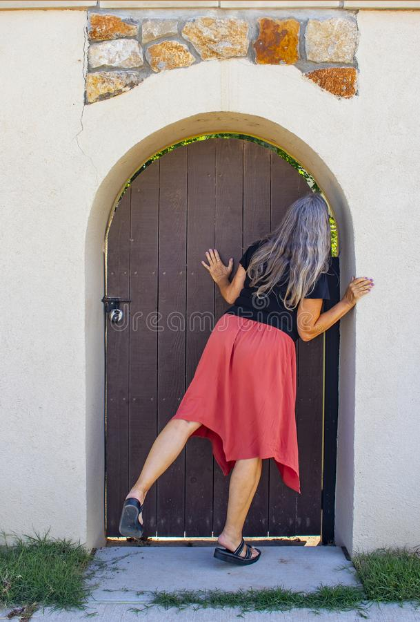 Woman with long grey hair peeks around locked arched door in wall to garden beyond stock photos