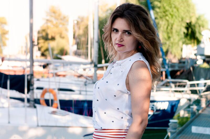 Woman with long hair in blouse standing and lookig at camera in front of sailboats. Attractive serios woman with long hair in blouse standing and lookig at stock photos