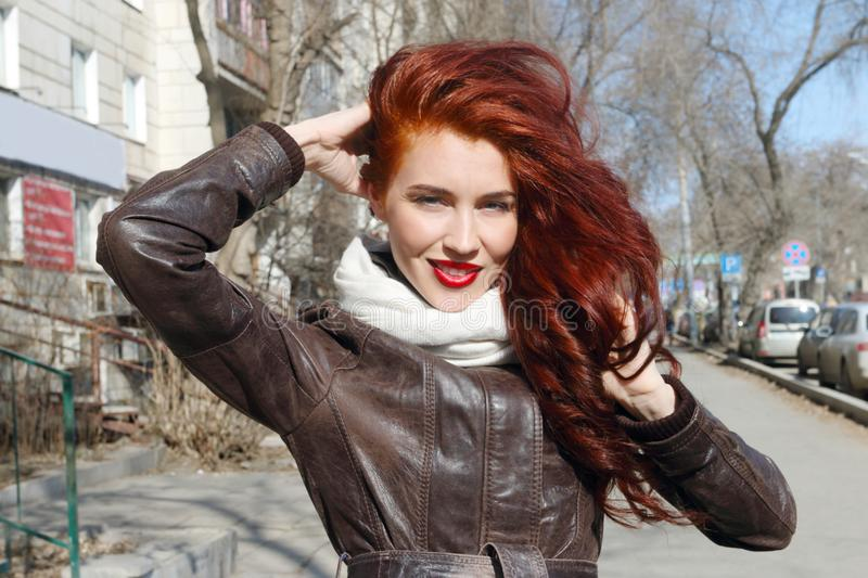 Woman with long hair in leather jacket smiles outdoor stock image