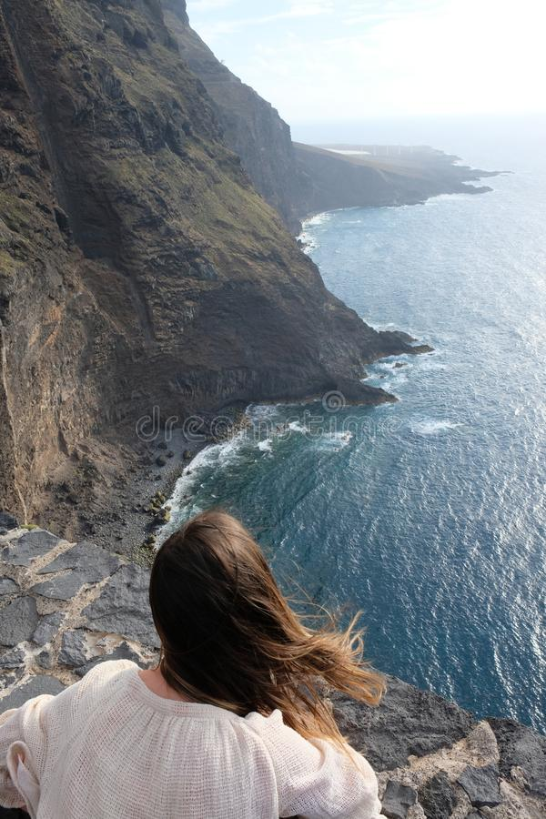 Woman with long hair looking to ocean cliffs from up above stock image