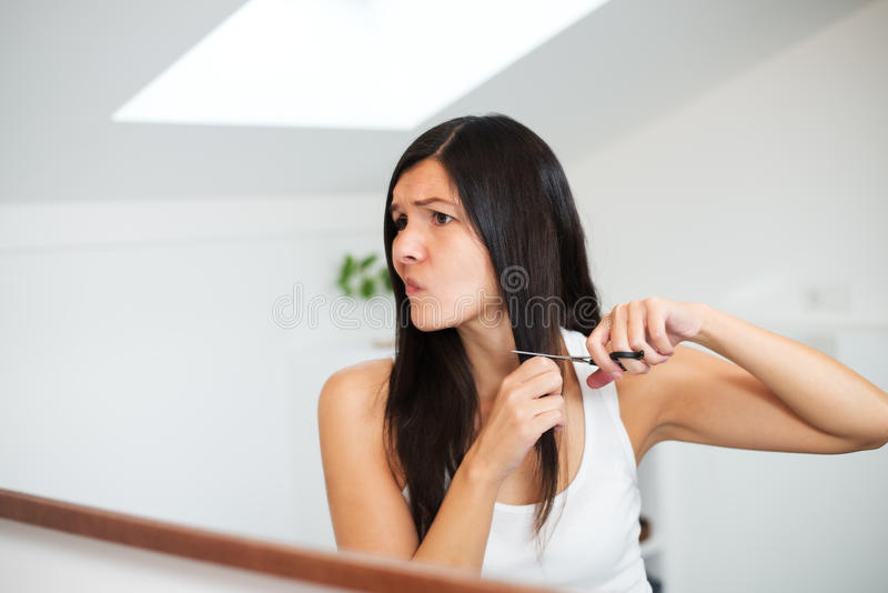 Woman with long hair preparing to cut it. Attractive young woman with long brunette hair preparing to cut it with a pair of scissors in the bathroom grimacing in royalty free stock image