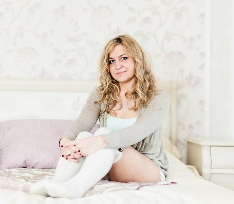 Woman with long hair smiling and sitting on bed royalty free stock photo