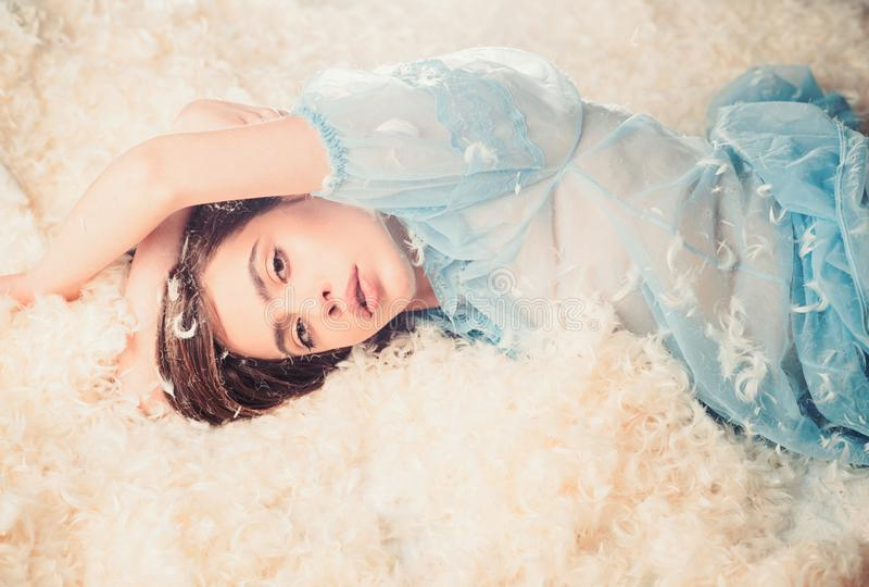 Woman with long hair in tender pajama relaxing. Girl on calm face lay on bed covered with feathers and fluff. Airiness. Concept. Lady in transparent blue royalty free stock image