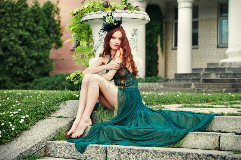 Woman with long legs in a green dress sitting on steps. royalty free stock photos