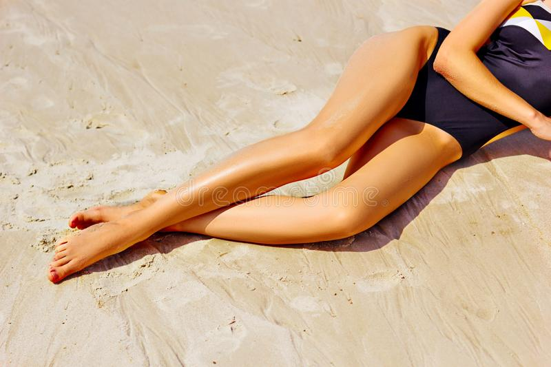 Woman with long legs on sand stock photos