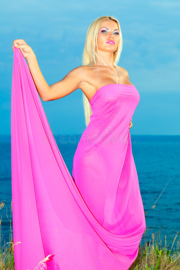 Woman in a long pink dress. stock photos