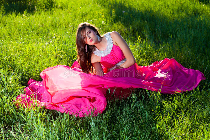 Woman in a long pink dress stock photography