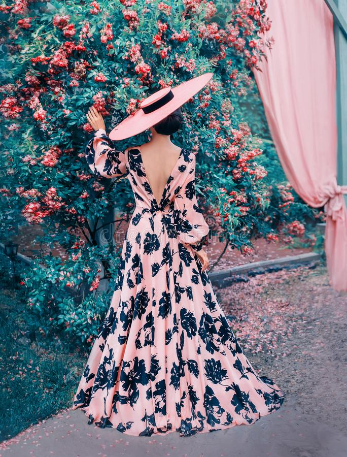 A woman in a long pink dress and a hat stands with her back to the camera royalty free stock photography