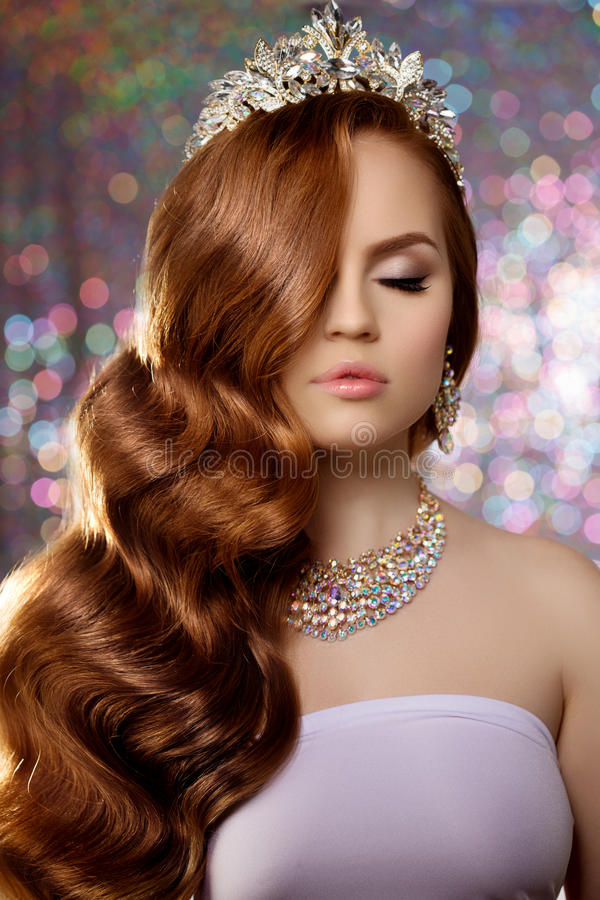 Woman with long red hair in lux dress crown, queen princess lights party background Luxury girl Long shiny healthy volume hair Wa royalty free stock photo