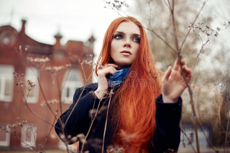 Woman with long red hair walks in autumn on the street. Mysterious dreamy look and the image of the girl. Redhead woman walking. In the autumn the city. Cold royalty free stock photos