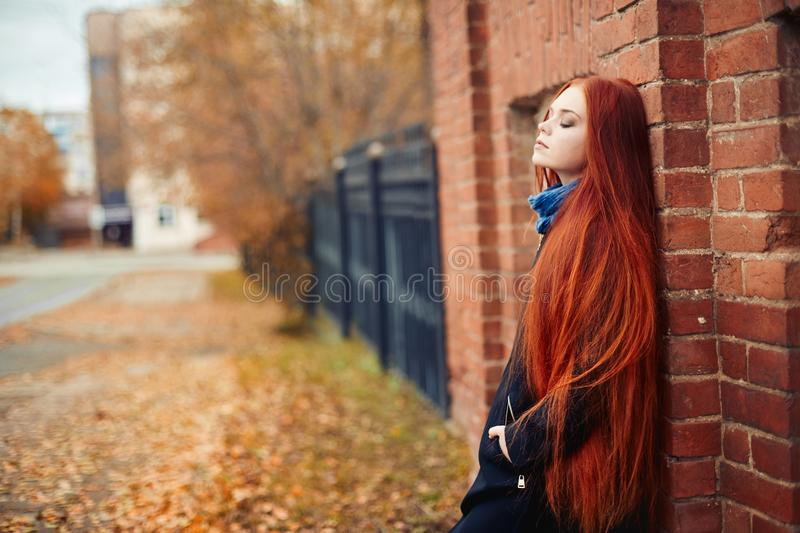 Woman with long red hair walks in autumn on the street. Mysterious dreamy look and the image of the girl. Redhead woman walking. In the autumn the city. Cold stock photos