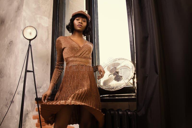 Woman in Long-sleeved Midi Dress Standing Near on Wall-mounted Fan stock photo