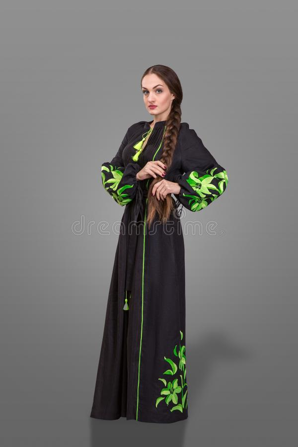 Woman with long stout pigtail wearing at long black embroidery with lime green ornament. Ukrainian fashion look over gray backgrou royalty free stock images