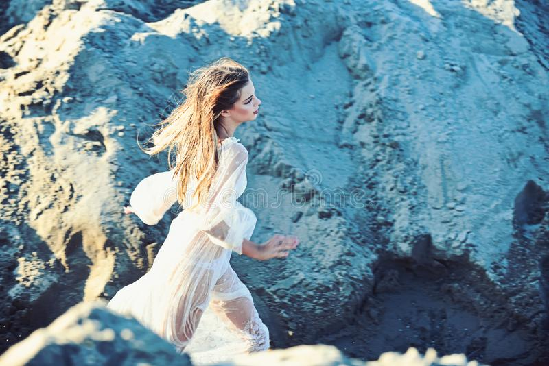 Woman with long wet hair run on sand dunes, energy. Woman in white dress on sunny day, fashion. Energy, activity, wellness. Fashion, beauty, hairstyle stock photography