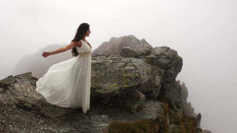 Woman in long white dress near abyss royalty free stock images