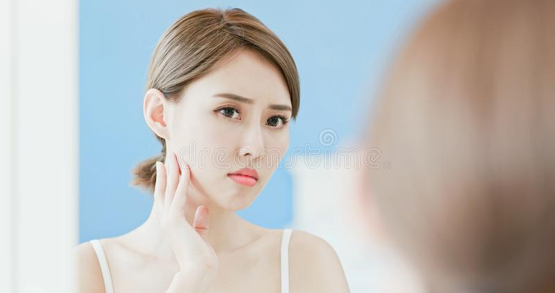 Woman with acne problem. Woman look mirrior feel upset and touch her face with acne problem stock photos
