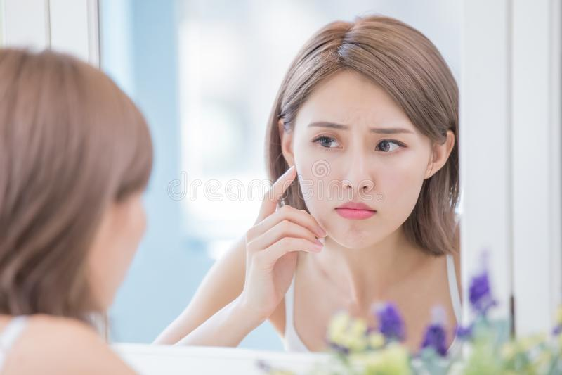 Woman with acne problem. Woman look mirrior feel upset and touch her face with acne problem royalty free stock photography