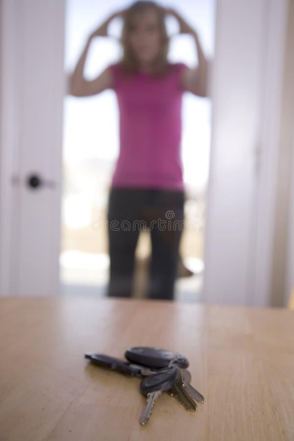Woman lookin at keys on table stock photo