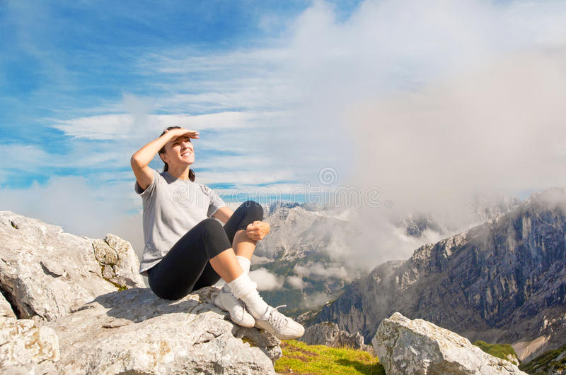 Woman looking ahead on top of the mountain royalty free stock photography