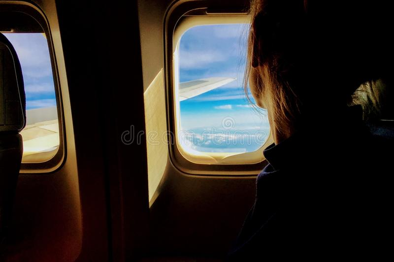 Woman looking through airplane window stock image