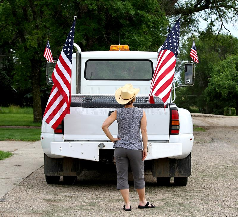 A woman looking at American flags displayed on a pickup truck. stock photo