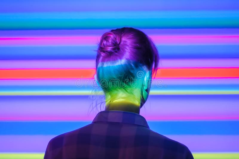 Woman looking around at modern exhibition with multi color light illumination royalty free stock photos